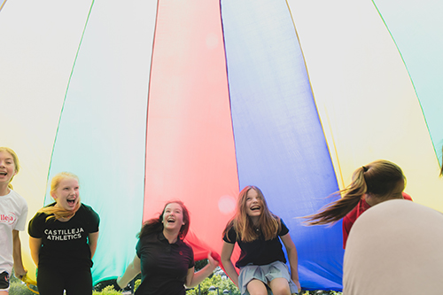 Girls laugh while playing with a parachute on the Circle